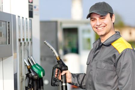 Glimlachende arbeider bij het benzinestation Stockfoto