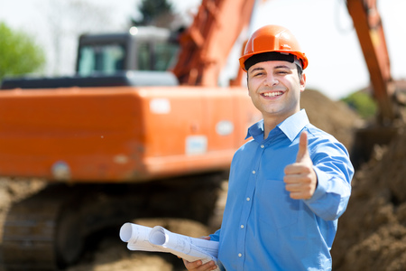 Architect showing ok sign in a construction site