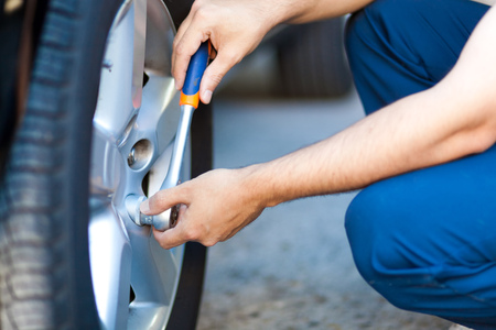 auto hoist: Auto mechanic in his workshop changing tires or rims Stock Photo