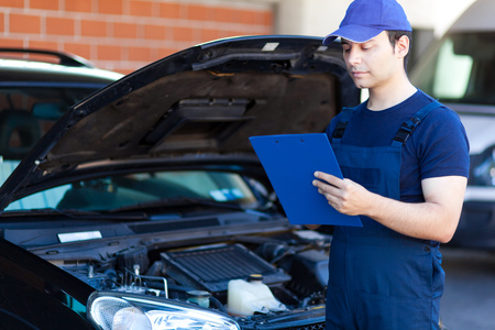 budget repair: Mechanic writing on a clipboard Stock Photo