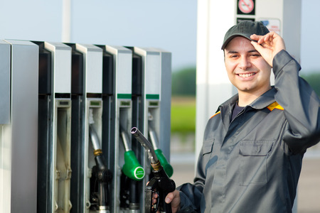 litre: Man holding a fuel nozzle Stock Photo