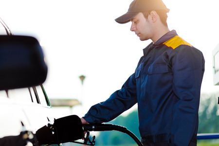 refilling: Gas station worker refilling car at service station