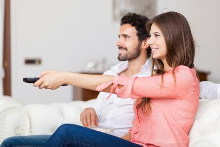 pareja viendo tv: Joven pareja viendo la televisión y comiendo palomitas de maíz