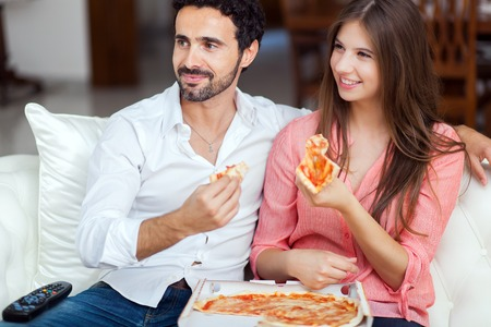 junks: Happy couple watching tv while eating pizza Stock Photo