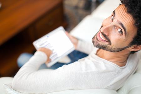 Uomo che utilizza una tavoletta mentre si distende sul divano Archivio Fotografico