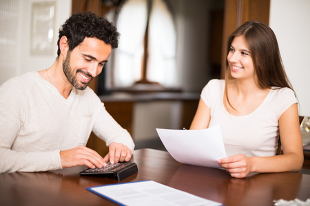 home expenses: Couple calculating their expenses together. Shallow depth of field, focus on the man Stock Photo