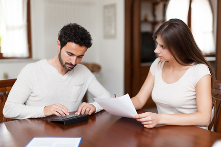 home finances: Tax, finances, family, home and happiness concept - busy couple with papers and calculator at home