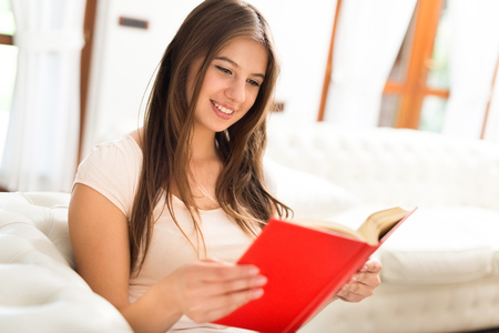 genres: Portrait of a woman reading a book while relaxing on the couch