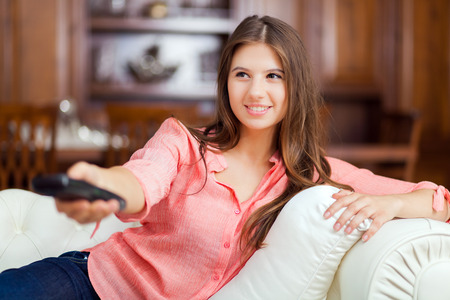 woman watching tv: Happy young woman watching tv on sofa