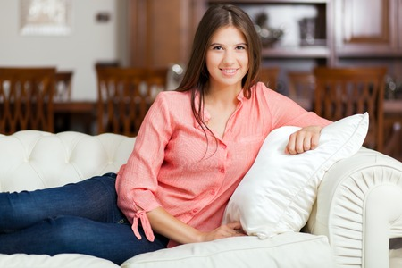woman lying: Relaxed young woman lying on couch Stock Photo