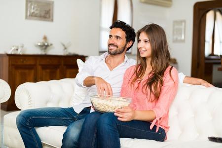 pareja viendo television: sonriente pareja feliz viendo la televisión. Poca profundidad de campo, se centran en la mujer