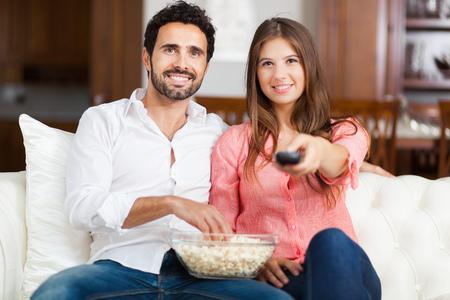 pareja viendo television: Joven pareja viendo la televisión y comiendo palomitas de maíz