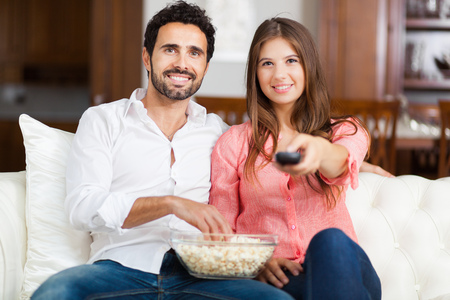 eating popcorn: Young couple watching tv and eating pop-corn