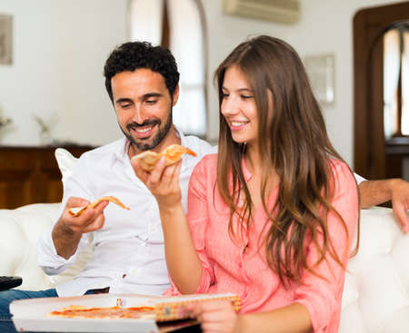 couple on couch: Smiling couple eating pizza while sitting on the couch Stock Photo