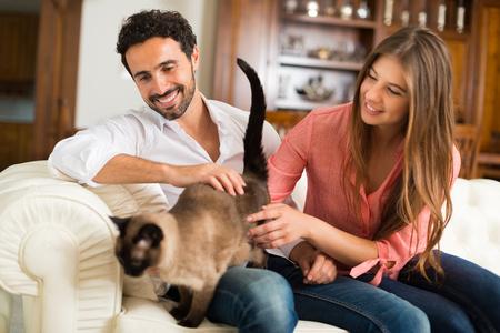 Portret van een gelukkig paar spelen met hun siamese kat op de bank. Ondiepe scherptediepte, gericht op de man
