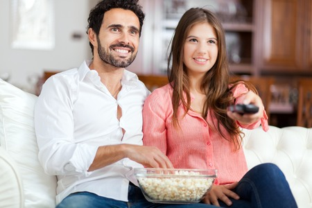 pareja comiendo: Joven pareja viendo la televisión y comiendo palomitas de maíz