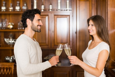 champagne flutes: Couple toasting champagne flutes in their apartment