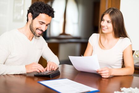 home expenses: Happy couple calculating their expenses together Stock Photo