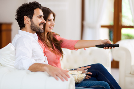 unhealthy living: Young couple watching tv and eating pop-corn