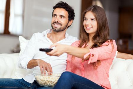 pareja viendo tv: Joven pareja viendo la televisi�n y comiendo palomitas de ma�z