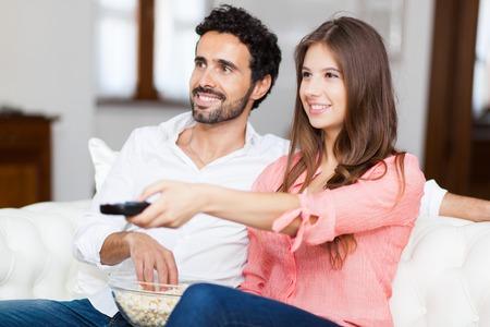 pareja viendo television: joven pareja viendo la televisión en un sofá