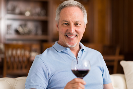 wine glass: Man holding a glass of red wine Stock Photo