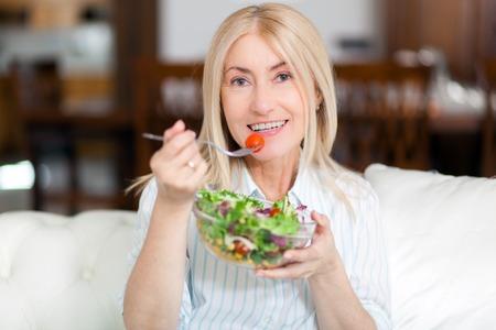그녀의 소파에 건강 샐러드를 먹는 성숙한 여인 스톡 콘텐츠