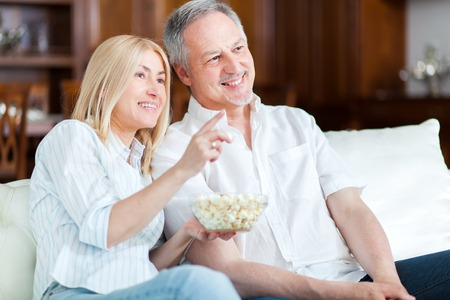 bluray: Couple eating pop-corn and watching tv Stock Photo