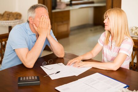 home expenses: Worried couple calculating their expenses together