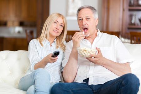 pareja viendo tv: pareja madura viendo la televisi�n mientras come palomitas de ma�z en el pa�s