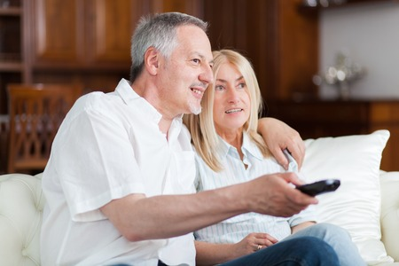 couple on couch: Senior couple sitting in couch and watching tv Stock Photo