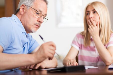 figuring: Senior couple working out their bills at home