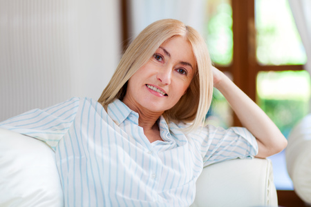 gleeful: Portrait of a smiling woman relaxing on the couch in her home