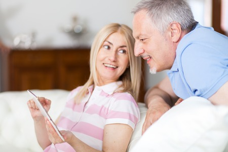 white interior: Portrait of an happy couple using a tablet