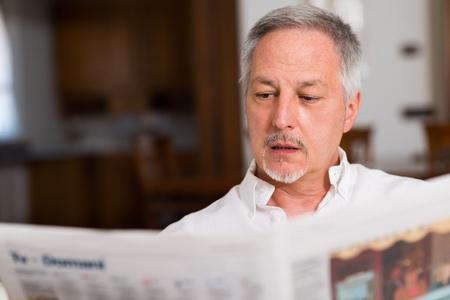 mature man: Portrait of a mature man reading a newspaper