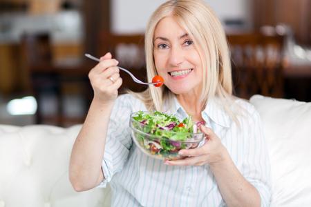 Rijpe vrouw zittend op een bank thuis, terwijl het eten van een salade Stockfoto