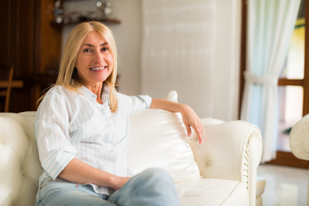 rich: Portrait of a smiling woman relaxing on the couch in her home