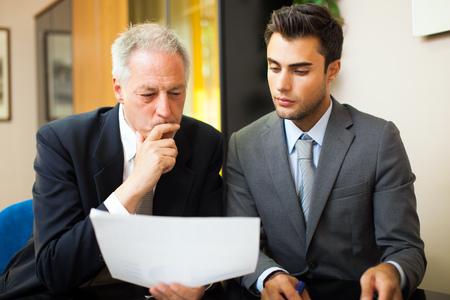 그의 동료에게 문서를 보여주는 사업가
