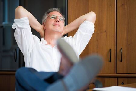 after work: mature man relaxing in his office after work Stock Photo
