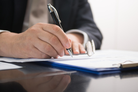 orthography: Detail of a businessman writing on a document