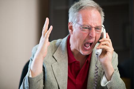 molesto: Retrato de un hombre enojado gritando en el teléfono