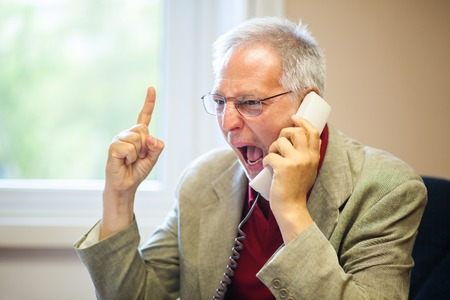 senior businessman: Angry senior businessman yelling at the phone