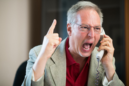 annoyed: Portrait of an angry businessman yelling at phone