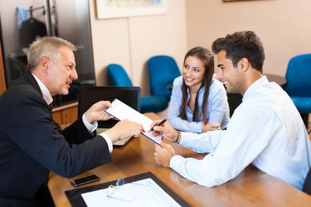 Senior Geschäftsmann zeigt ein Dokument, um ein Paar zu unterzeichnen Standard-Bild - 60118059