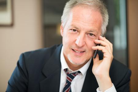 Ritratto di un uomo d'affari sorridente senior che comunica sul telefono nel suo ufficio Archivio Fotografico