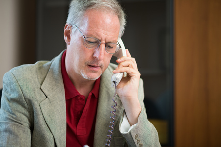 mature business man: Portrait of a businessman talking on the phone