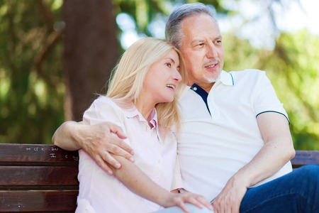 man sit: Happy mature couple sitting on a bench Stock Photo