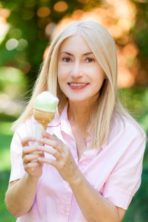 Mature woman eating an ice cream at the park