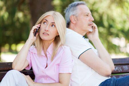 lovers quarrel: Senior couple sitting back to back talking on mobile phones Stock Photo