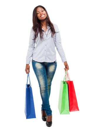 compras compulsivas: Beautiful black woman smiling and holding shopping bags